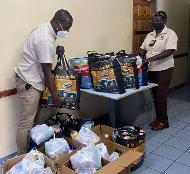 Two representatives of the TTPS Community Policing Unit, Tobago Division, package hampers courtesy a partnership with bmobile for distribution to needy Tobagonians.