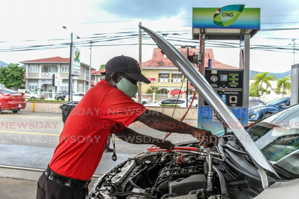 Pump attendant Subhan Mohammed fills a vehicle with CNG at St Christopher's Service Station on Wrightson Road, Port of Spain.  - PHOTO BY AYANNA KINSALE