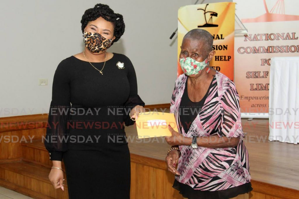 Minister of Sport and Community Development Shamfa Cudjoe  presents Norma Lewis with her grant at the at the Mt. Hope/ Mt. Lambert Community Centre, Community Drive, Riverside Avenue in San Juan.  Photo by Ayanna Kinsale