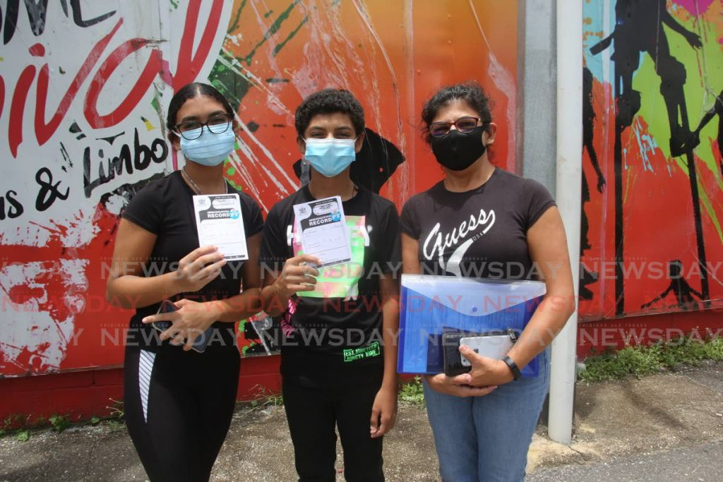 Mayah Mohammed, 15, left, and her brother Andrew Mohammed, 12, with their mom Salina Amow after the children received their Pfizer covid19 vaccines at the Paddock, Queen's Park Savannah, Port of Spain, Wednesday. Photo by Sureash Cholai
