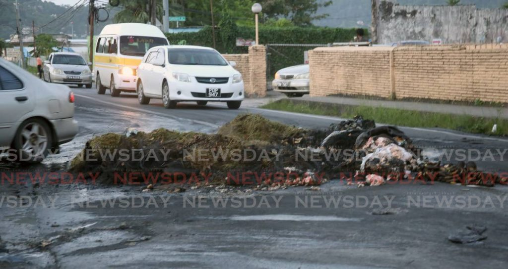 Remnants of a fiery protest by Covigne Road residents partially block the Diego Martin Main Road on Wednesday evening. Residents were reacting do the death of Jonah Gordon earlier that day. - SUREASH CHOLAI