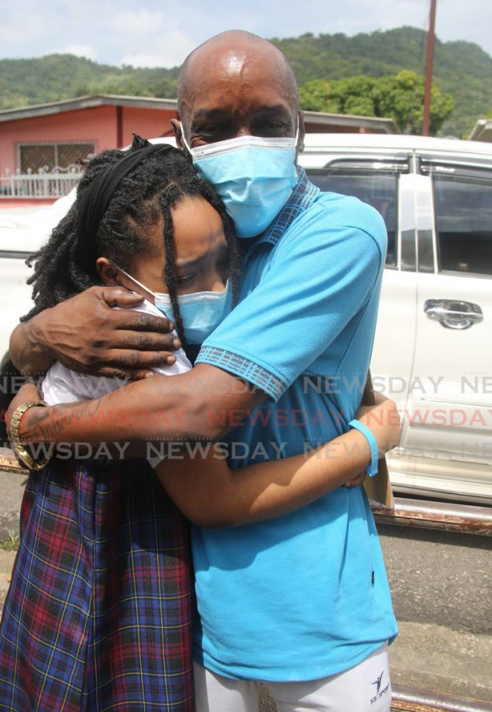 Diamond Vale Government Primary School student Adifa Farrell hugs her father Lester Farrell after receiving her SEA exam result on Thursday. - Photo by Sureash CholaI