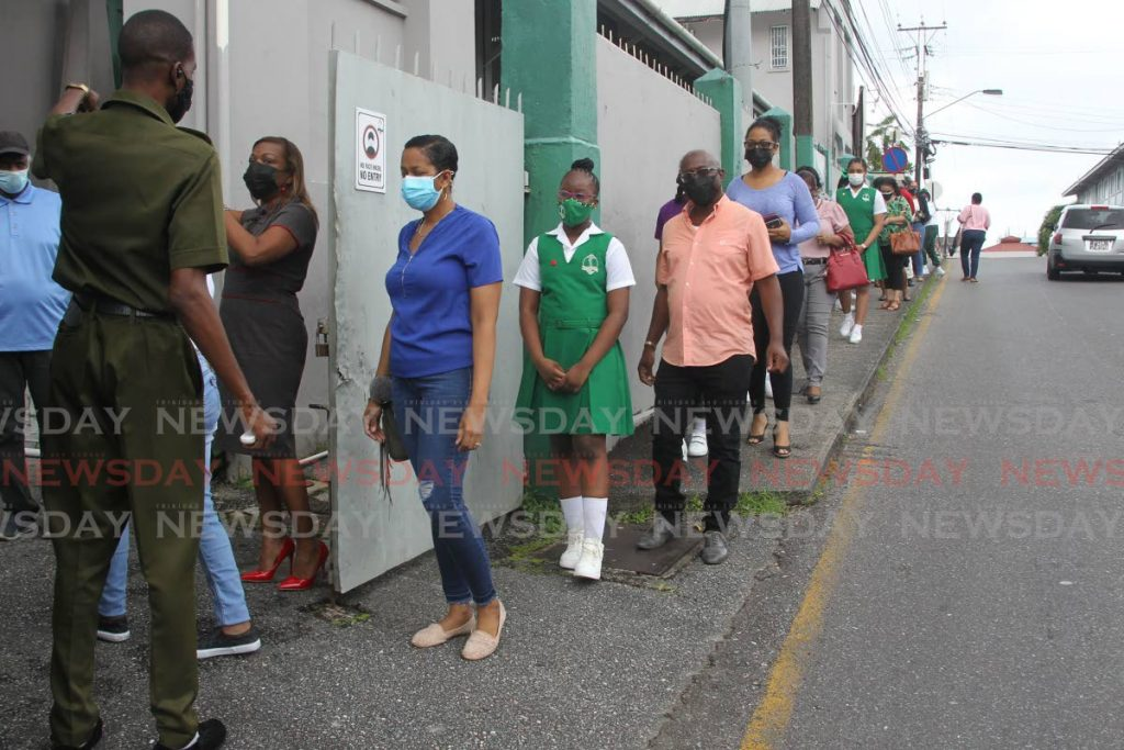 Parents and their daughters line up outside St Gabriel's Girls Primary School in San Fernando to collect the 2021 SEA results on Thursday. - PHOTO BY LINCOLN HOLDER