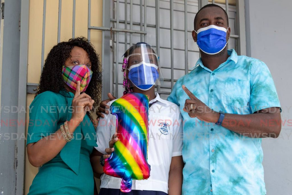 Scarborough Methodist Primary School student Jole St John placed first among Tobago students in the SEA examination. She is supported by her parents Kevin Small, left, and Trillicia St John on Thursday. - PHOTO BY DAVID REID