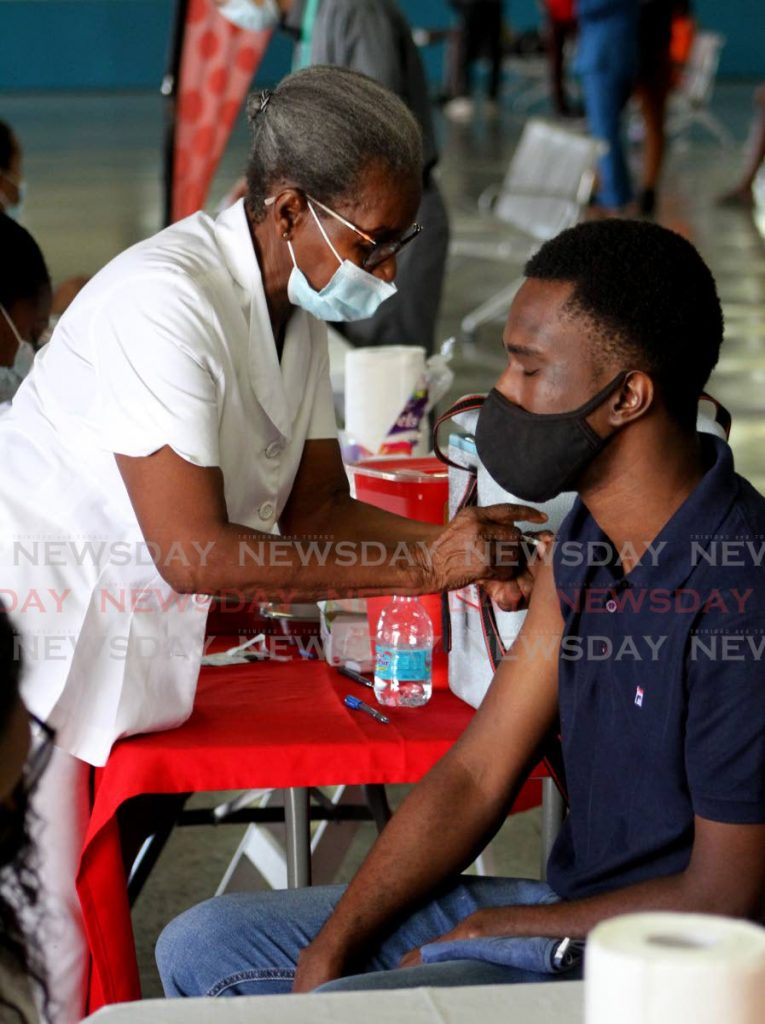 Retired Nurse Ivy Thompson gives Nicholai Antar his shot of the Johnson & Johnson covid19 vaccine at the NWRHA One Shot and Done drive, City Gate, Port of Spain on Friday morning. - Photo by Angelo Marcelle