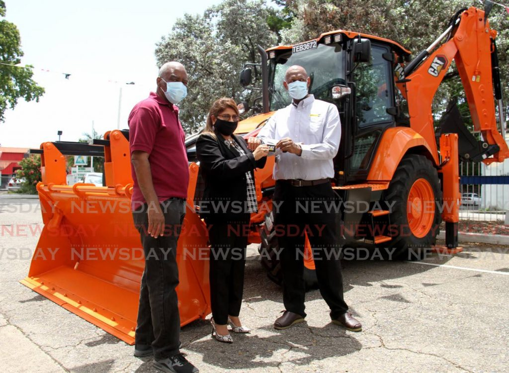 San Juan Laventille Regional Corporation CEO Diane Lakhan receives the key to a backhoe from Massy Machinery Equipment Consultant Anthony Sanchez at the MTS Plaza, Aranguez Main Rd, San Juan. Also in the photo is Chairman Anthony Roberts - Photo by Ayanna Kinsale