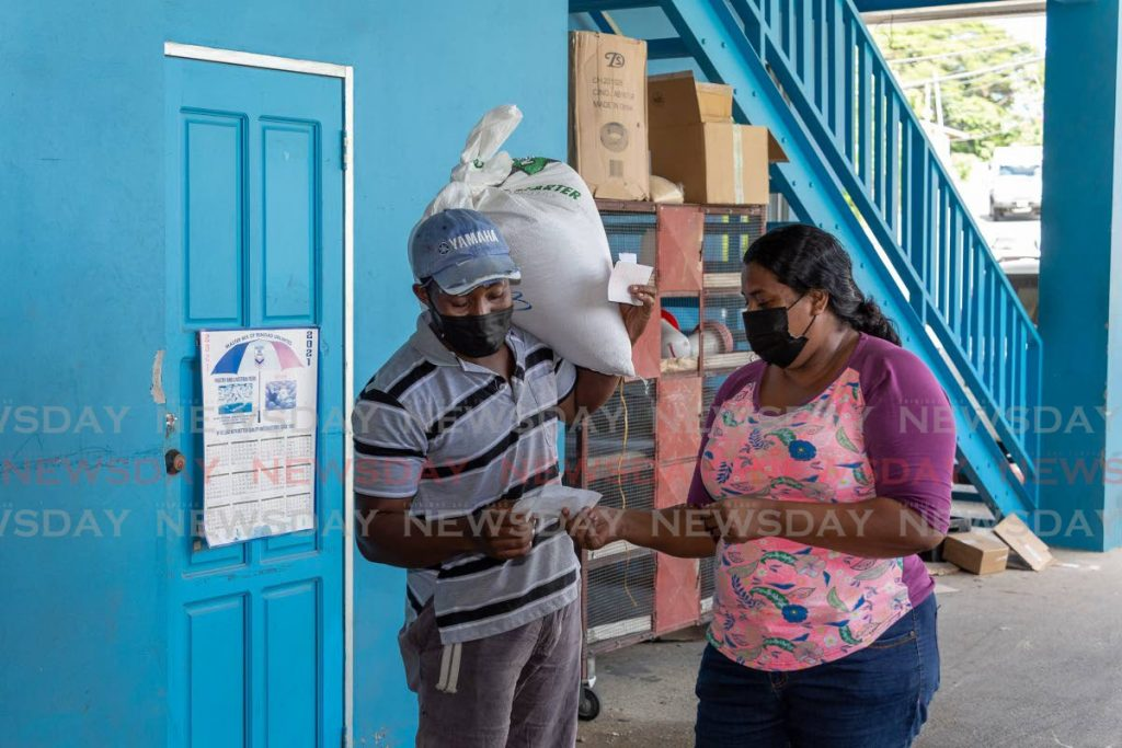 Davila Boodram, right, drove from Speyside village to buy starter feed for her chickens and dog rice from Mt Grace Feed Depot Ltd, Mt Grace, Tobago on Saturday. Scarborough/Mt Grace is one of the 15 electoral districts proposed in the EBC Order. - PHOTO BY DAVID REID