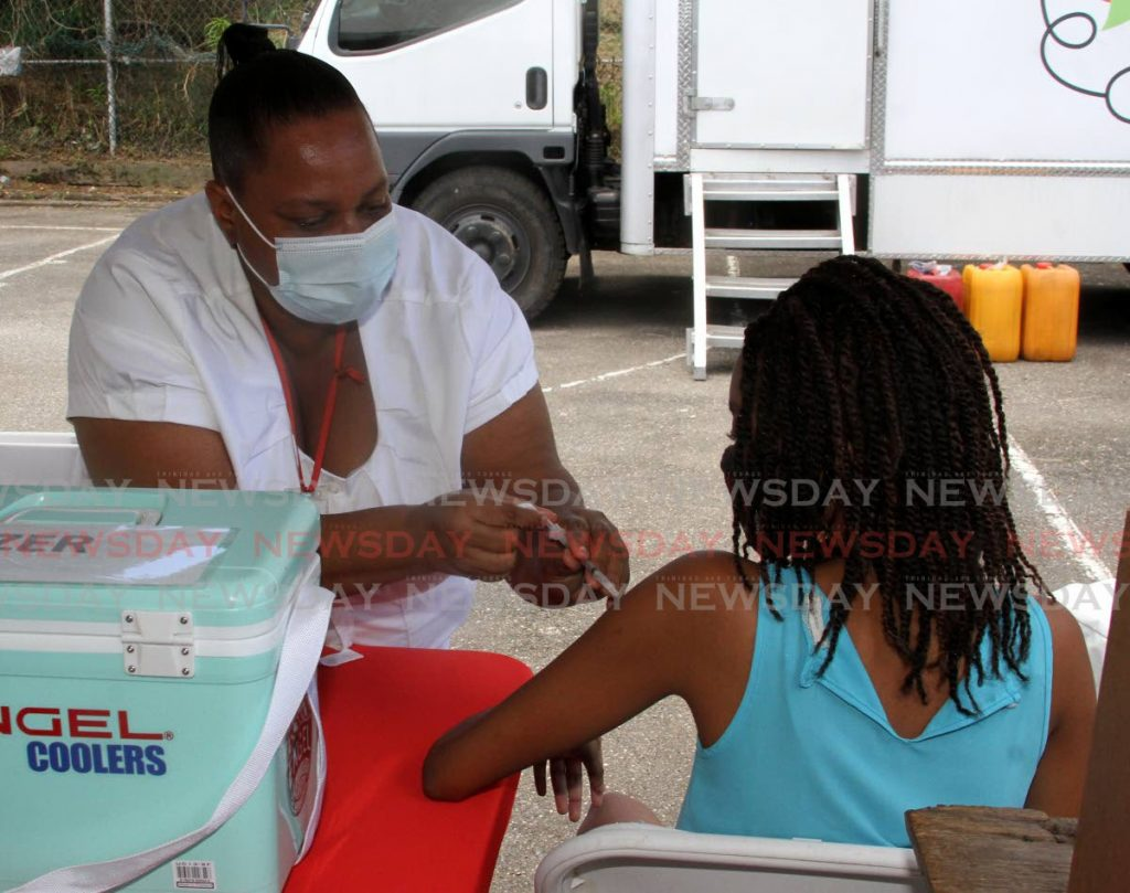 Registered nurse Patricia Nurse administers the Pfizer covid19 vaccine to Kevatia de Silva, 14, during the vaccination drive at St Barbs Basketball Court, Laventille on Saturday.  -Photo by Angelo Marcelle