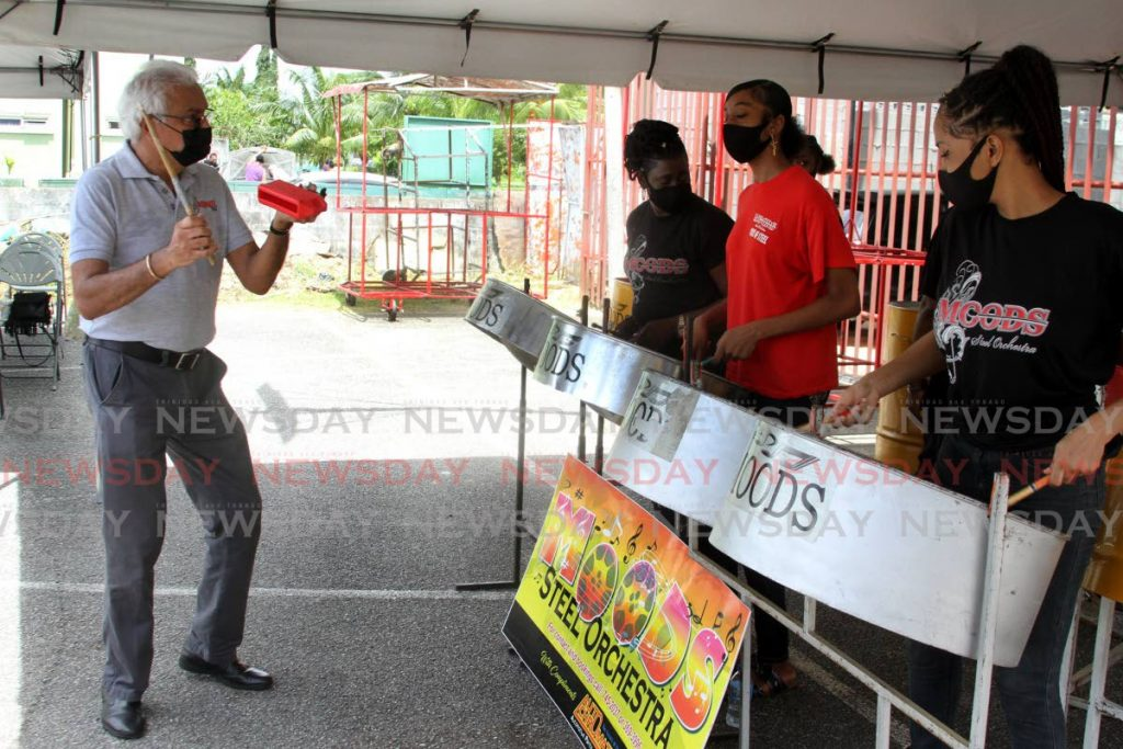 Minister of Health Terrence Deyalsingh plays a toc toc and dances to the sound of music by Moods Steel Orchestra playing Trouble In The Morning at a vaccination drive held at East Grove, Eastern Main Road, Curepe on Sunday. - Angelo Marcelle