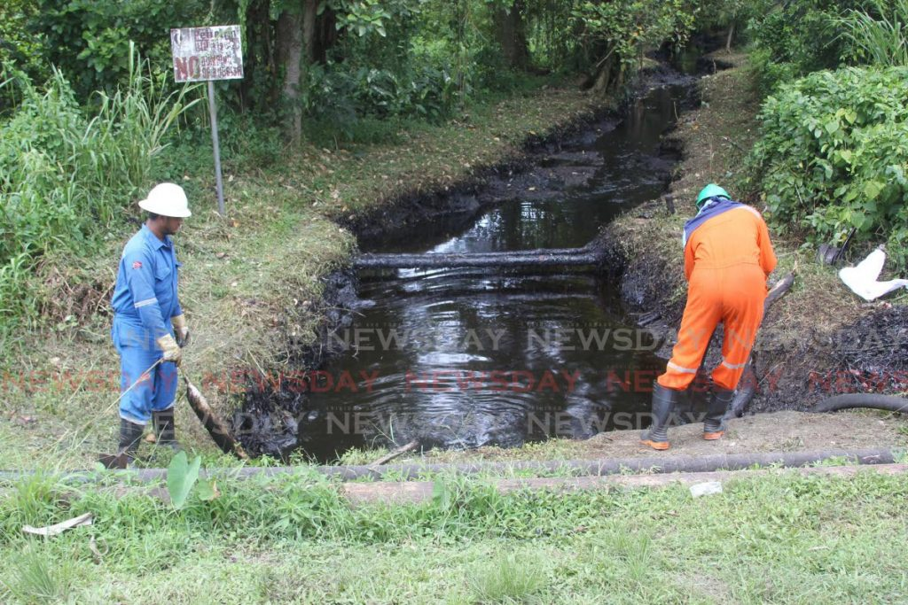 Workers from Quintana services install an oil containment boom in a river in Point Ligoure, Point Fortin following an oil leak. Heritage Petroleum Company Ltd is investigating the source of the leak. - Photo by Lincoln Holder