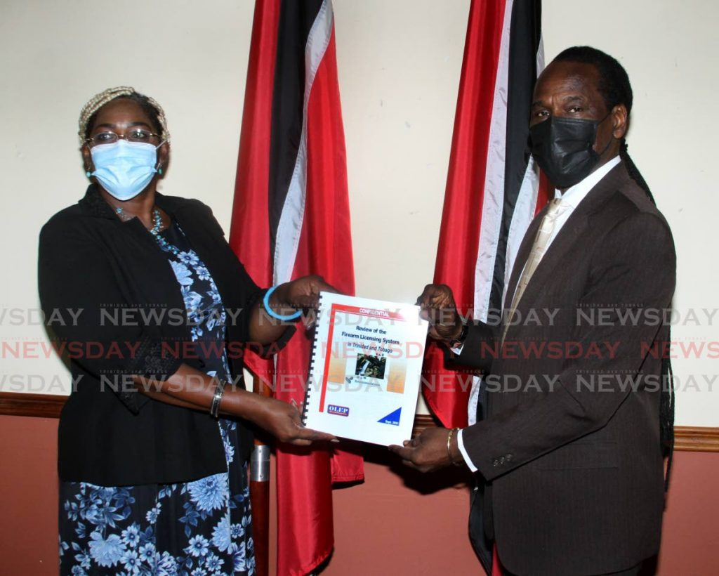 Director of the Organisation of Law Enforcement Policy Gale Charles, hands over the FUL system review to Minister of National Security Fitzgerald Hinds, at the Ministry of National Security, Water Front Centre, Port of Spain on Tuesday. - Photo by Angelo Marcelle