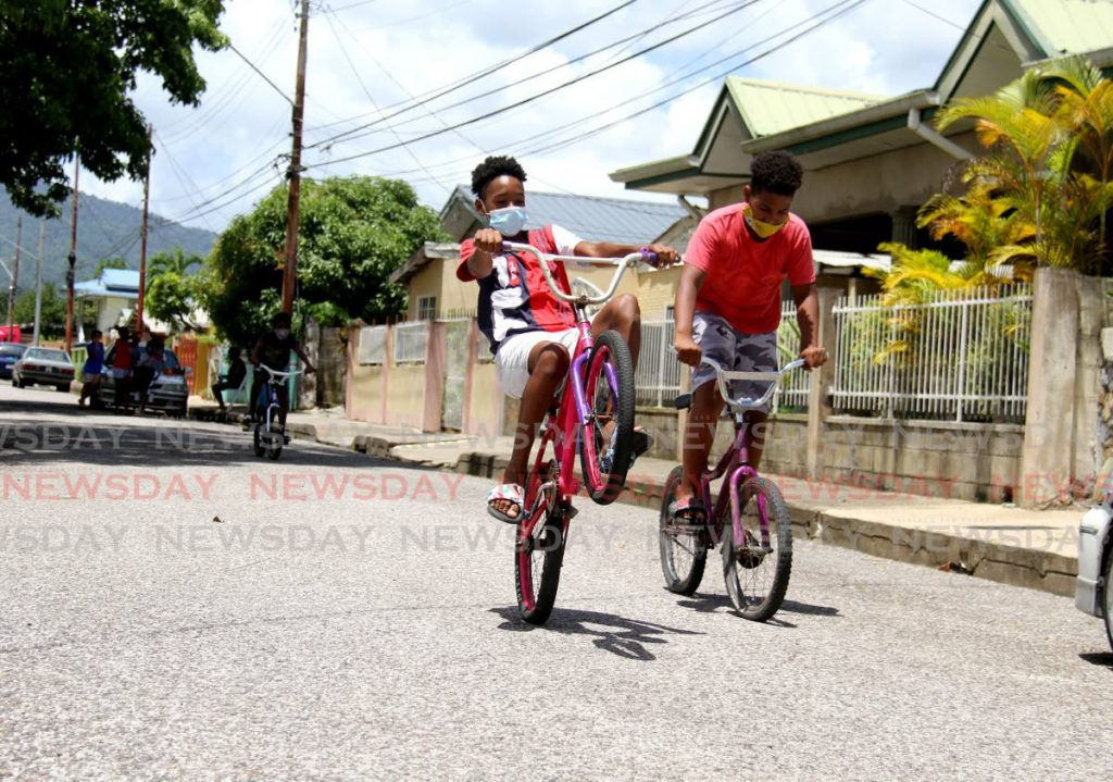 Deshaun Headley shows off his wheelie skills as he rides his bike with his friend Javon Alleyne on Croton Lane, Malabar on Tuesday. The boys enjoyed their free time after their online classes.  - Photo by Ayanna Kinsale