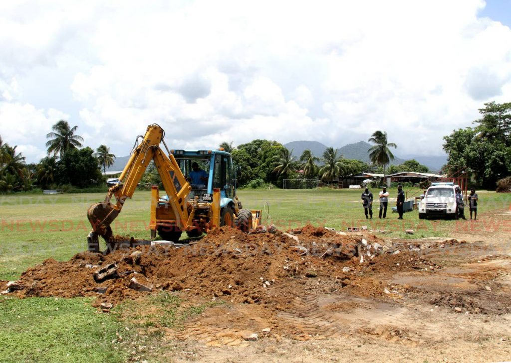 Police look on as a backhoe operator, of the Arima Borough Corporation, clears debris of the demolished pavilion on a playing field, located at the corner of Croton Lane and Gardenia Drive, Malabar, on Tuesday. Photo by Ayanna Kinsale