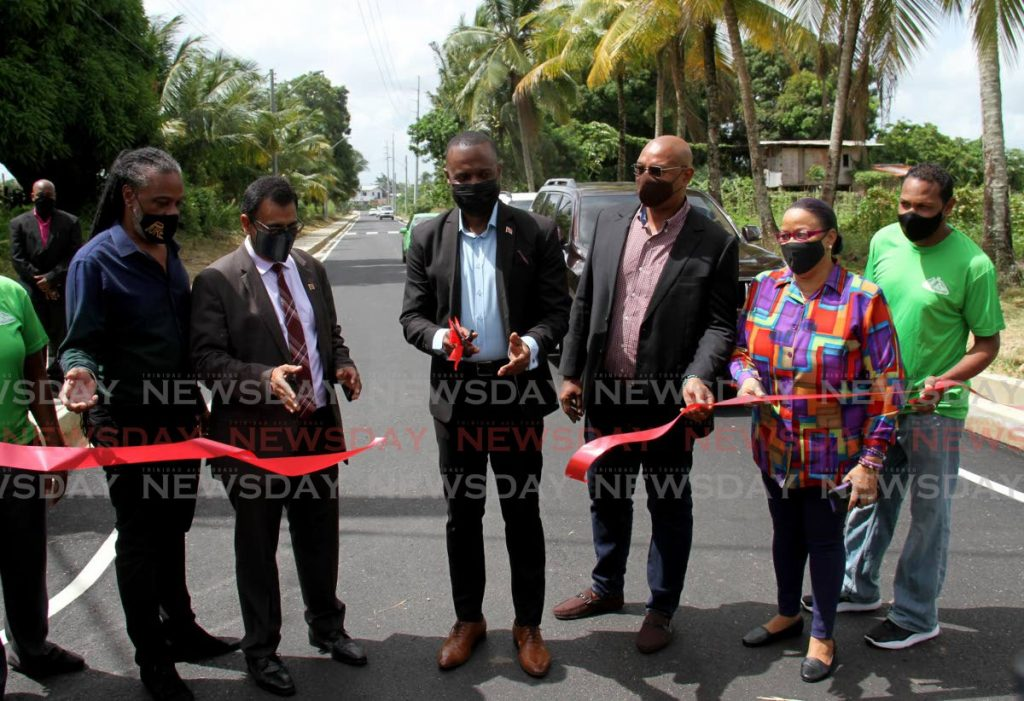 Public Utilities Minister Marvin Gonzales, centre, cuts the ribbon to officially open the newly paved Windy Hill Road in Arouca on Wednesday.  - Photo by Ayanna Kinsale