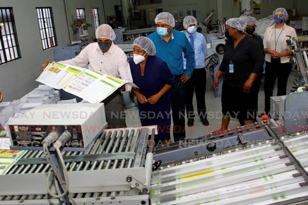 Sales manager Isa Mohammed shows Trade and Industry Minister Paula Gopee-Scoon a printed leaflet that will be processed into a booklet for a client at Eniath's Printing Co Ltd, Eteck Industrial Park, Caroni. - PHOTO BY ROGER JACOB