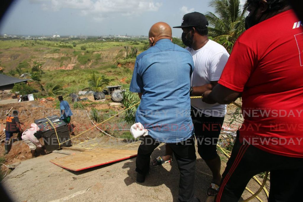 Neighbours and friends of Giles Garcia help him remove appliances from his home which collapsed because of a landslip at Diamond Road, Claxton Bay. - Lincoln Holder