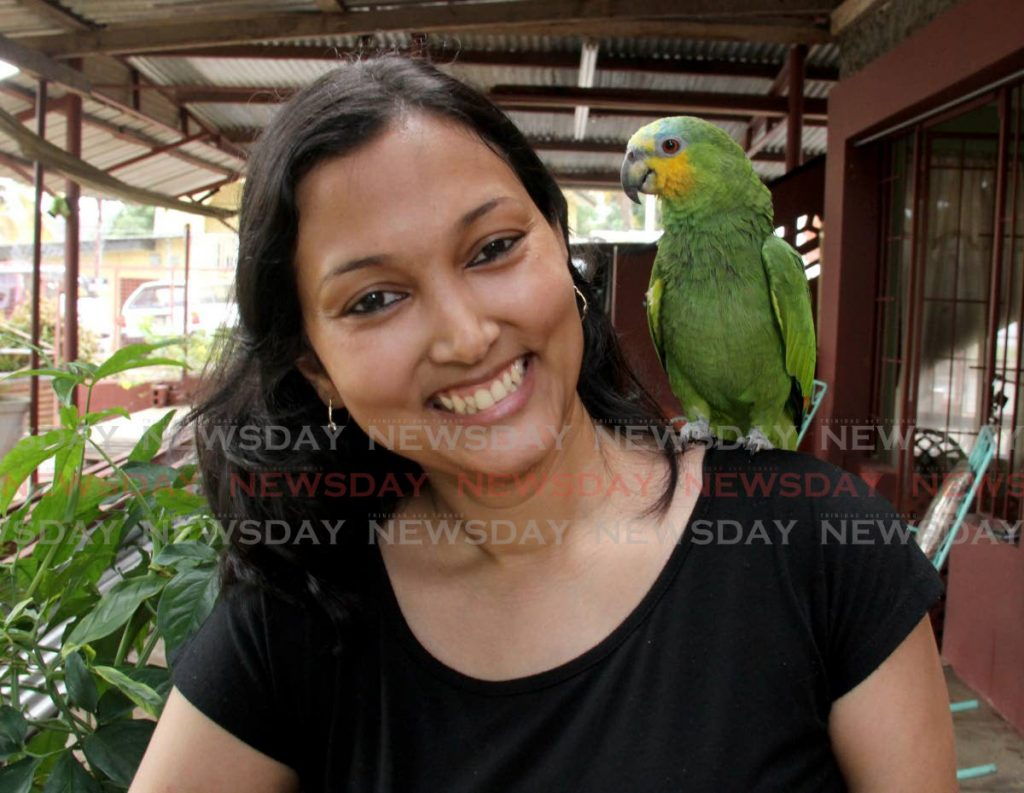 Bird sitter Tricia Boodoo shares a joke with her pet parrot, Parrot, at her home in St Joseph. - AYANNA KINSALE