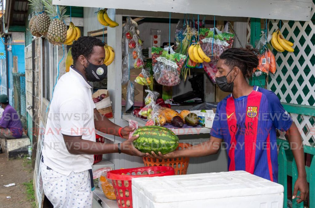 Vendor Donnell Burris, right, hands customer Adrian Adams a watermelon purchased  at his new vegetable and produce stall in Mason Hall, last weekend.  - Photo by David Reid