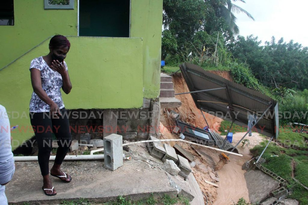 Marva Fritz shows Newsday the new areas of erosion at the back of her house after the weekend rainfall at Diamond Road Claxton Bay on Monday. - ROGER JACOB
