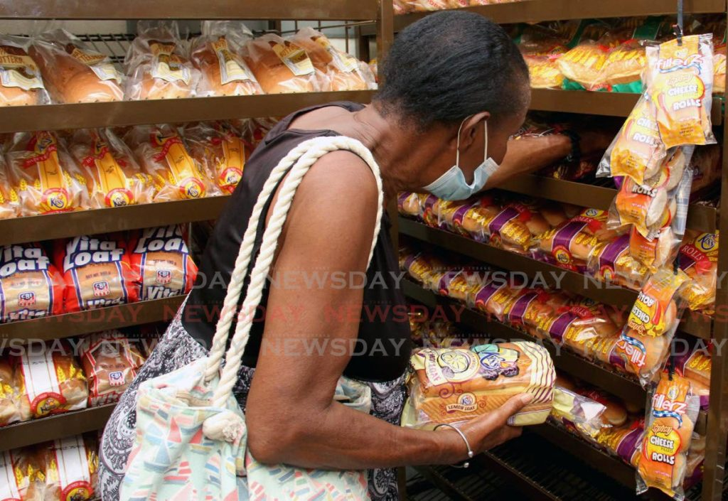 A woman selects a Kiss specialty bread at Back to Basics Supermarket, Port of Spain. Photo by Ayanna Kinsale