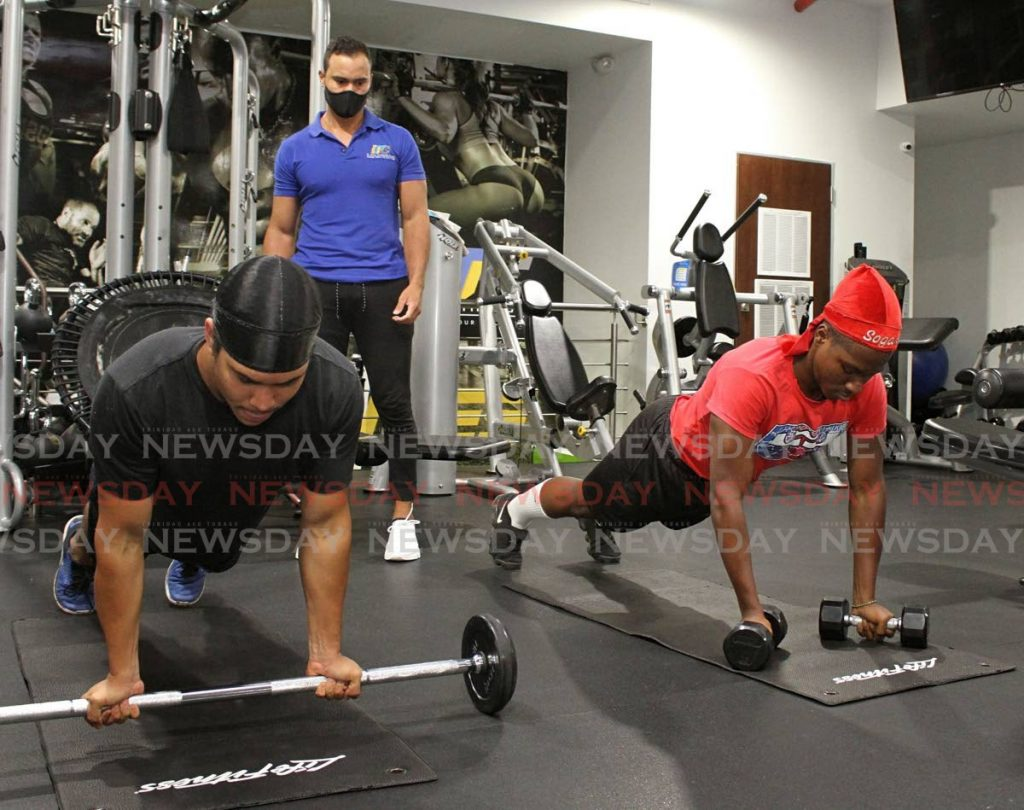 In this June 23 file photo, Hans Kappel (left) and Odunmbku Somorin exercise under the keen eye of instructor Alejandro Figueroa (background), at D Dial Fitness gym, Arima. - Angelo M. Marcelle