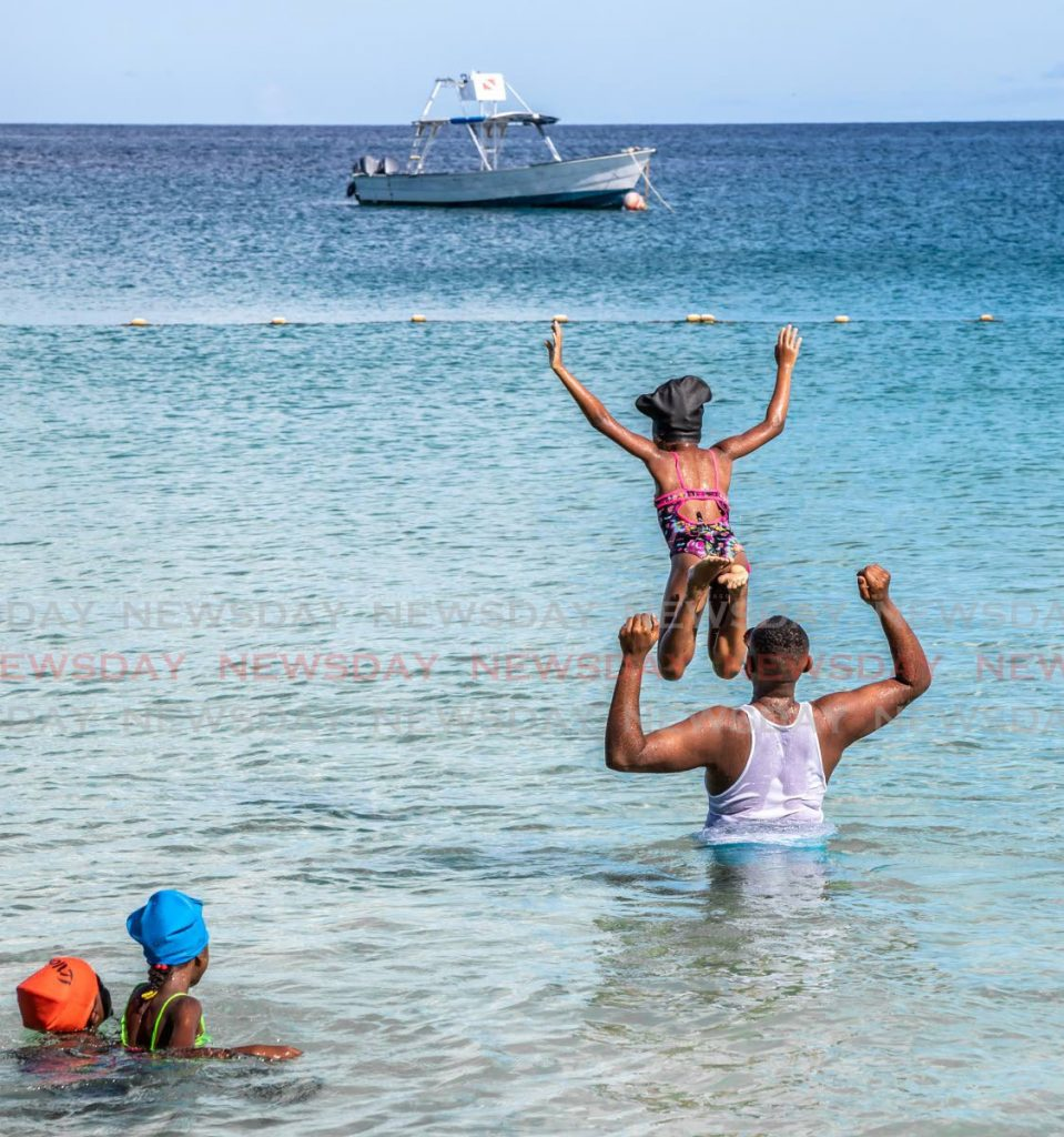 In this file photo, Paul Hospedales is on vacation with his three daughters in Store Bay Tobago. In his 2022 budget presentation, finance minister Colm Imbert announced that Tobago will receive an allocation of $2.357 billion to manage its affairs in the upcoming fiscal year. $50 million will be allocated to Tobago's tourism and hotel sector. Photo by Jeff K Mayers