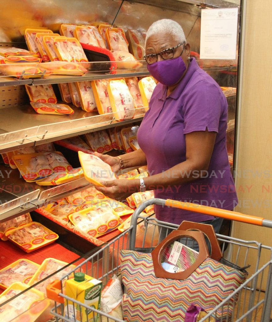 In this file photo, a customer picks up a pack of chicken at Massy Stores, Mandalay, Arima. - Angelo Marcelle