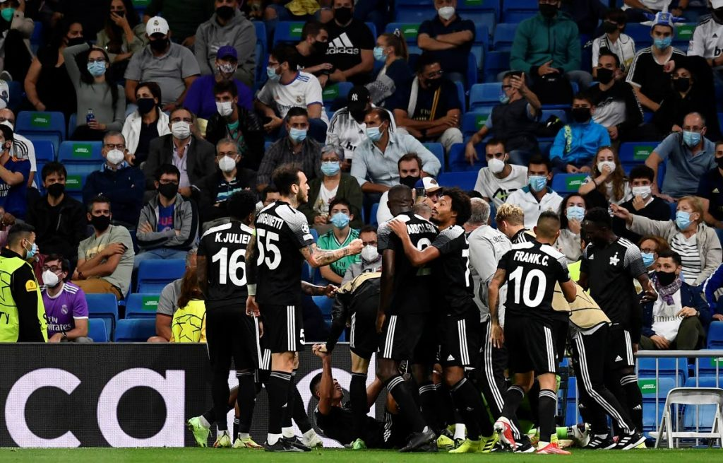 Sheriff's Sebastien Thill celebrates with teammates after scoring his side's second goal during the UEFA Champions League group D match between Real Madrid and Sheriff Tiraspol at the Bernabeu stadium in Madrid, Spain, on Tuesday. Trinidad and Tobago's Keston Julien is at left (#16). AP PHOTO -