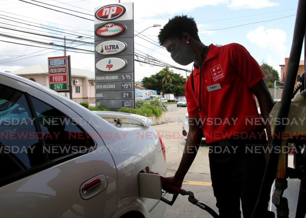 In this file photo, gas pump attendant Trey Marcelle fills a vehicle with gas at the St. Christopher's Service Station on Wrightson Road, Port of Spain. - Photo by Ayanna Kinsale