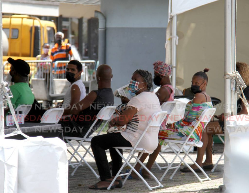 Citizens sit in the observation area after receiving the Johnson and Johnson vaccine at the vaccination drive at the Brian Lara Promenade.  - Photo by Ayanna Kinsale