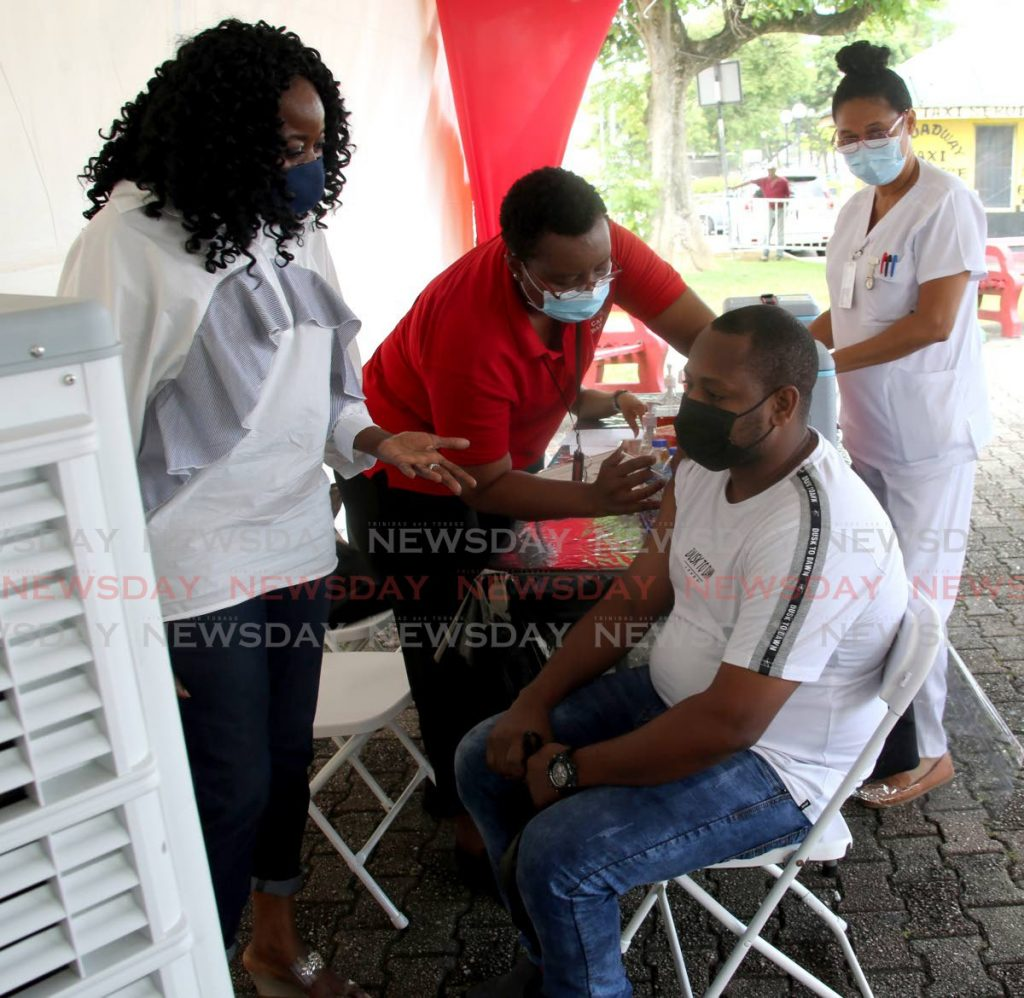 Social Development Minister Donna Cox chats with Dillon Belgrove as he receives the Johnson and Johnson one-dose vaccine on the Brian Lara Promenade, Port of Spain on Saturday. - PHOTO BY SUREASH CHOLAI