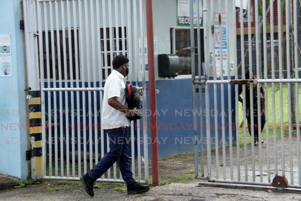 A student of Mucurapo Secondary School walks into the compound on the first day of school. School reopened on Monday for vaccinated students who are in forms four, five and six. - Photo by Ayanna Kinsale