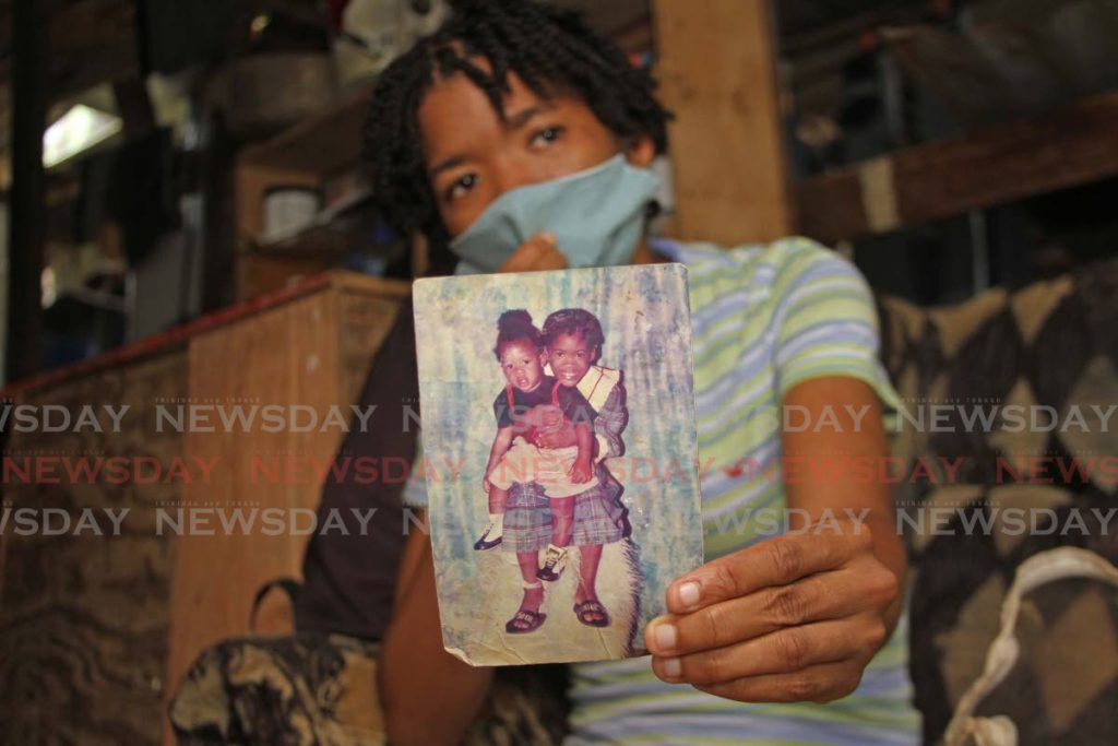ShellyAnn Pierre, sister of 20-year-old Samuel Pierre, shows Newsday a photo of happier times with her brother. Samuel fell into the Cipero River on Friday and drowned. -  Photo by Marvin Hamilton