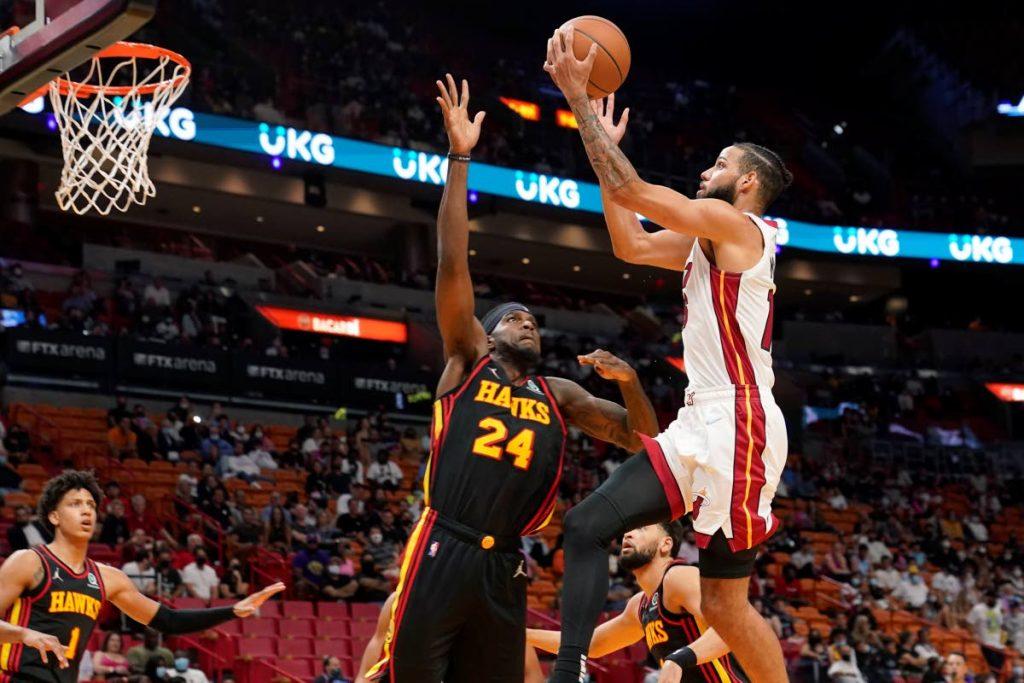 In this photo taken on Monday, Miami Heat forward Caleb Martin drives to the basket as Atlanta Hawks Trinidadian centre Johnny Hamilton (24) defends during the second half of a preseason NBA basketball game, in Miami.  - (AP PHOTO)