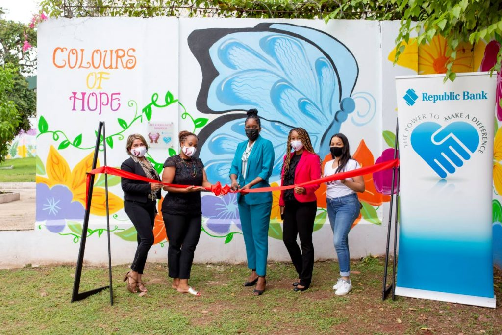 Natalie Burnette-Alfred, senior official, CSR management and stategic support, Republic Bank, centre, with Anika Plowden-Corentin, founder/creative director Chosen Hands, second from left, and the Chosen Hands team cut the ribbon to unveil the Colours of Hope Mural at the St Jude's Home for Girls in Belmont. -