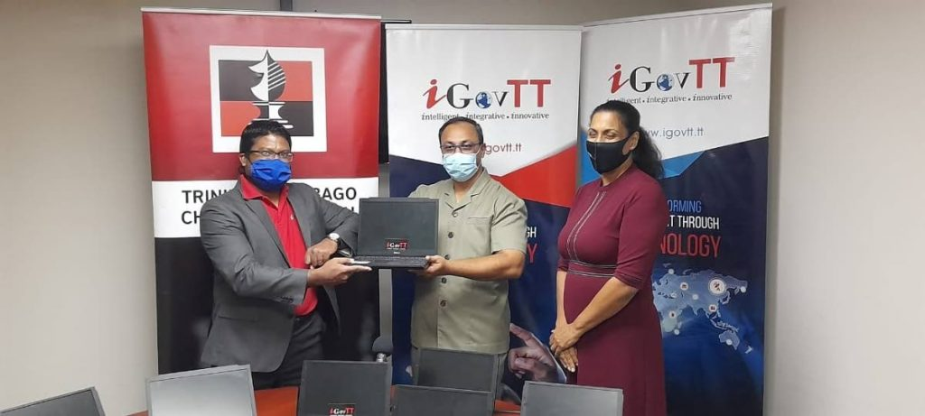 iGovTT acting deputy CEO Sherwin Ragoonanan, left, presents acting Supt. of Prisons Allan Nanan with ten laptops for prisoners' use at the Inter-Continental Chess Championships next week. At right is local chess association president Sonja Johnson. - TTCA