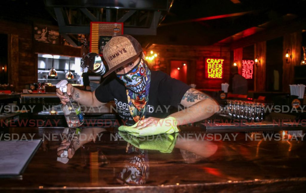 Barman Andrea Roass cleans the counter of Tommy's Bar in MovieTowne, Port of Spain in preparation for the opening of safe zones next Monday. PHOTO BY SUREASH CHOLAI -