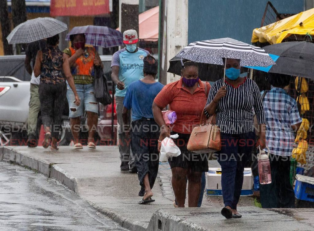Pedestrians use umbrellas to shelter from the heavy rain on Friday while some walked through unbothered along Carrington Street, Scarborough. - David Reid