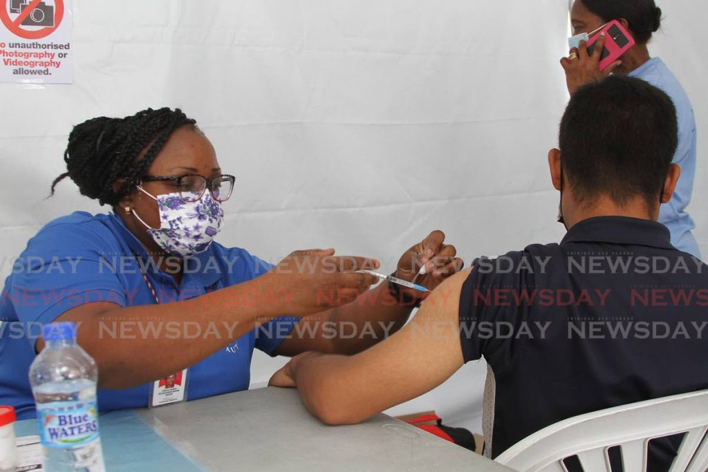 A nurse vaccinates a man at the South West Regional Health Authority's covid19 vaccination drive on the promenade in Princes Town on Saturday. With cases increases, public health officials again encourage the public to get vaccinated. - Photo by Marvin Hamilton