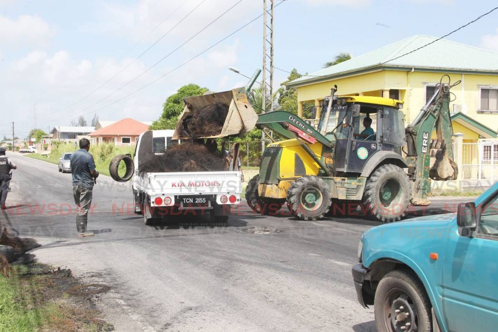 Workers from the Penal/Debe Regional Corporation remove debris from the Rochard Douglas Road in Barrackpore after residents staged an early-morning protest over bad roads. - Photo by Lincoln Holder