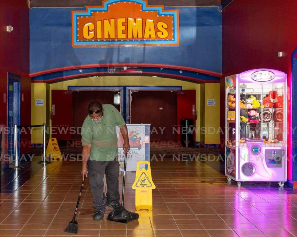 Carlon Garrick, a maintenance  employee of Movie Towne, Gulf City Mall, Lowlands, cleans in preparation for reopening earlier this week. PHOTO BY DAVID REID  -