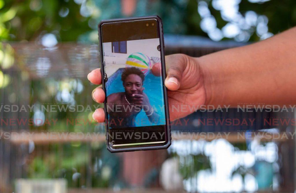 An aunt of murder victim Nikel Matthews shows his photo on her cellphone on Monday. - David Reid