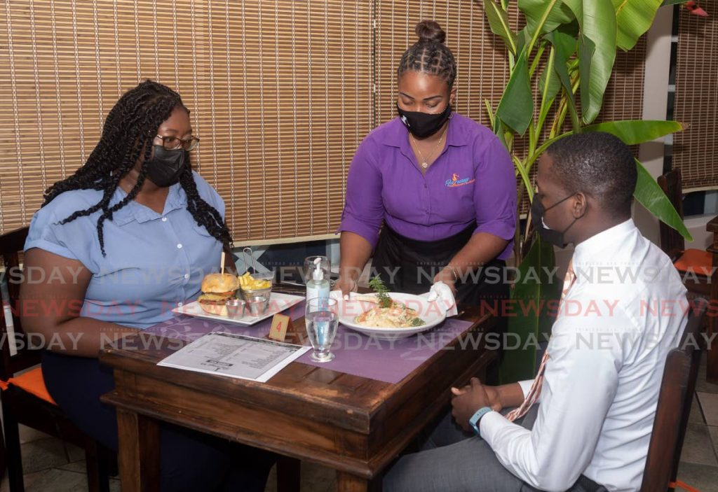 DINNER IS SERVED: In this file photo, friends Shenee Winchester and Anthony Springer enjoy dinner at Fairways Restaurant and Golf Lounge at Tobago Plantations, Lowlands, on Monday. The restaurant reopened as a safe zone, allowing dine-in for vaccinated customers only. - Photo by David Reid
