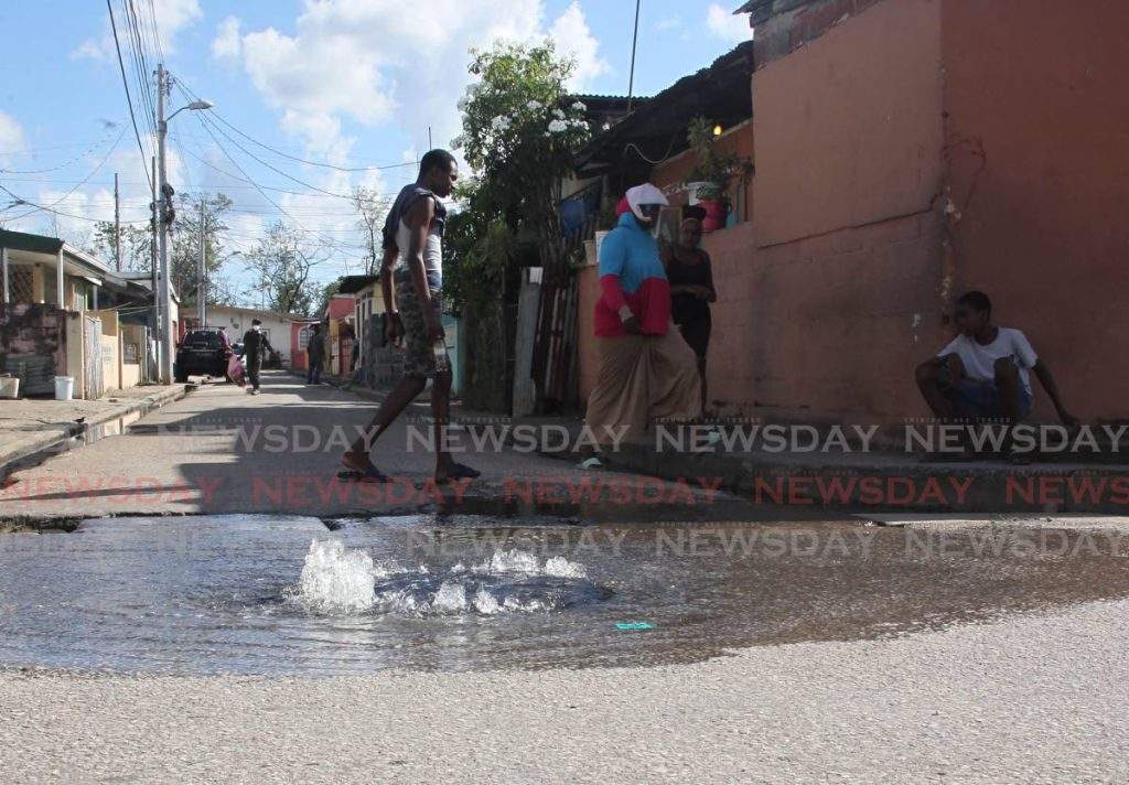 A man walks past a manhole from which sewage has been gushing at Main Street, Beetham Gardens. - ROGER JACOB