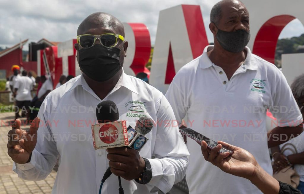 Curtis Douglas, left, vice president of the All Tobago Fisherfolk Association, speaks with reporters in Scarborough on Tuesday. - David Reid