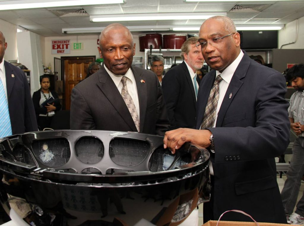Former US ambassador to TT John Estrada and G-pan and PHI inventor Dr Brian Copeland inspect the frame for a PHI (percussive harmonic instrument) at UWI. Photo taken from tt.usembassy.gov -