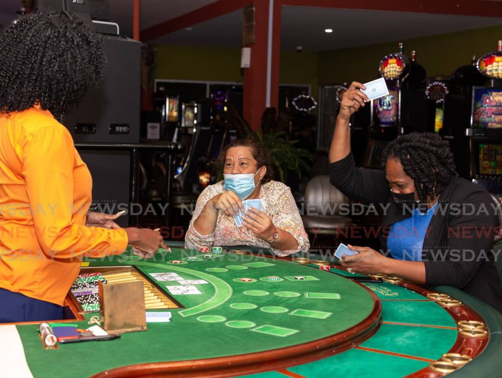 WINNER: Allison Thomas, right, of Black Rock slams her card on the table as she plays a game of rhum 32 alongside Allisa Martineau of Mt Pleasant at Silver Dollar Casino, Shirvan Plaza, Shirvan Road, Tobago, on Wednesday. - David Reid
