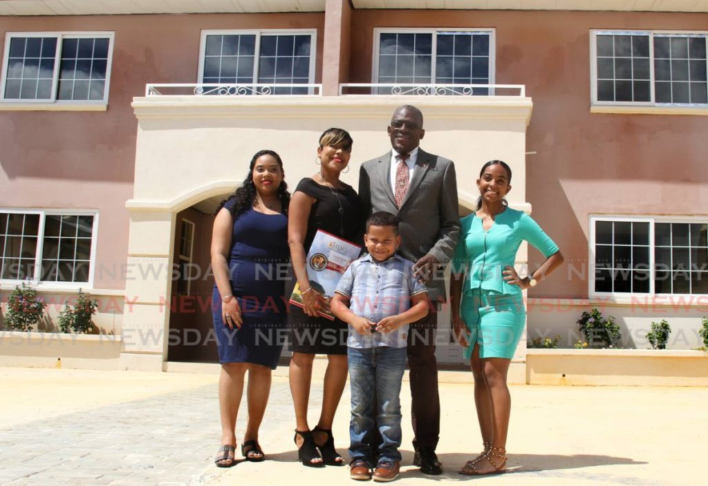 In this 2020 file photo, former housing minister Edmund Dillon takes a photo with Shelley-Ann Williams and her children at a key distribution held at Trestrail Lands, D'Abadie. In his budget presentation on October 4, Finance Minister Colm Imbert said the Housing Development Corporation (HDC) would be restructured so that its landlord function will be separated from its function as a builder of affordable houses. - PHOTO BY AYANNA KINSALE
