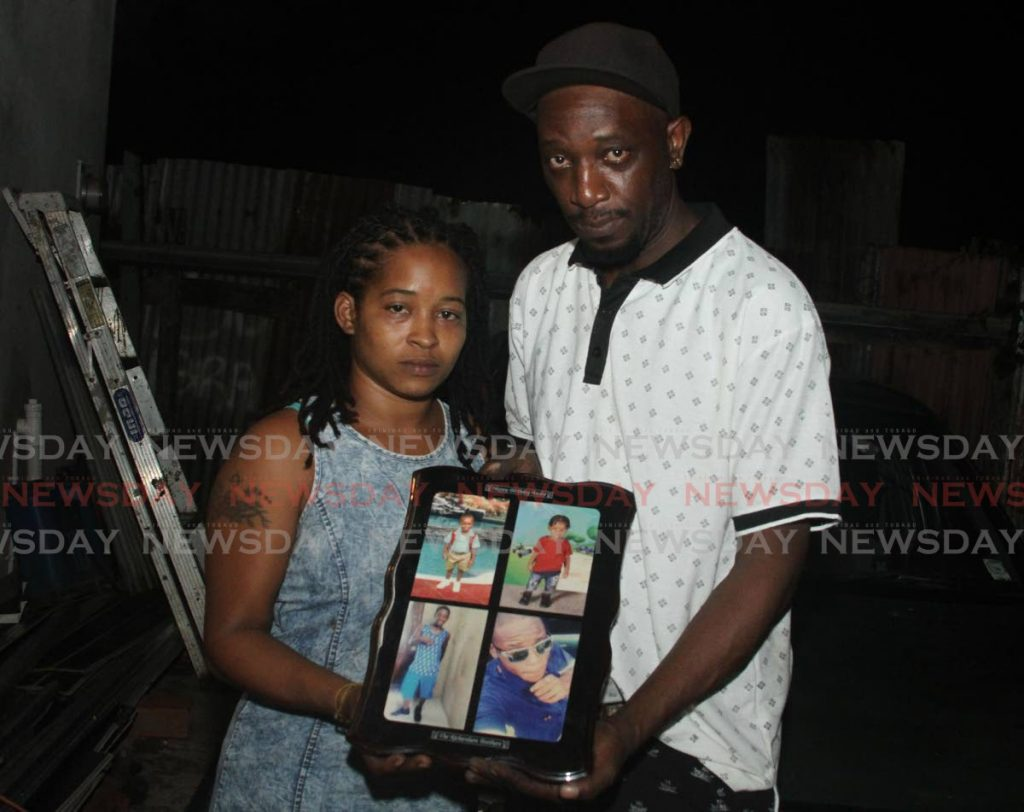 Crystal Paponette and Andre Richardson, the parents of Yasin Richardson, hold  a plaque with photos of their children at their home. - Ayanna Kinsale